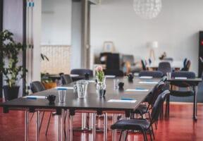 Konferenční uspořádání stolů s nápoji a bloky v prostoru Galerie v Riegrově 51