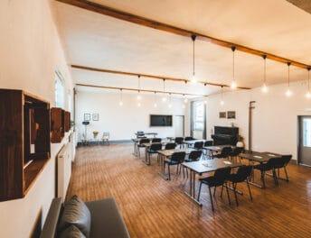 Záběr zezadu na prostor Kavárny Riegrovy 51 ve školním uspořádání