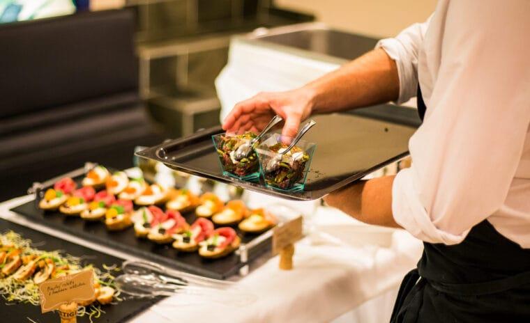 Číšník doplňující pokrmy na rautový stůl